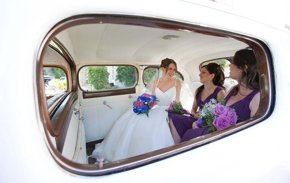 Mariée avec filles d'honneur dans une voiture ancienne