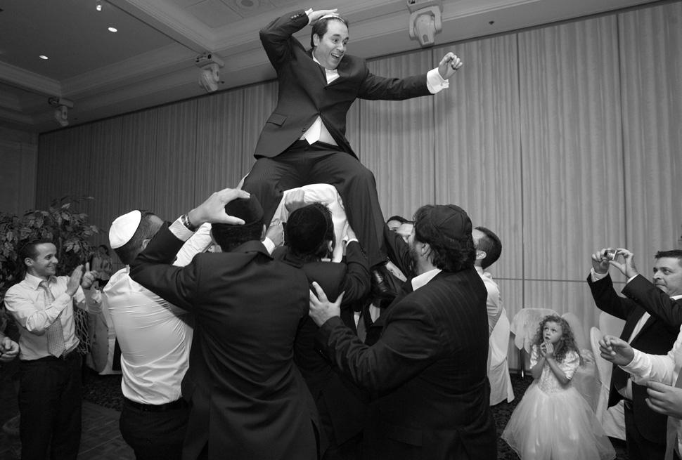 Groom on a chair during hora dance.