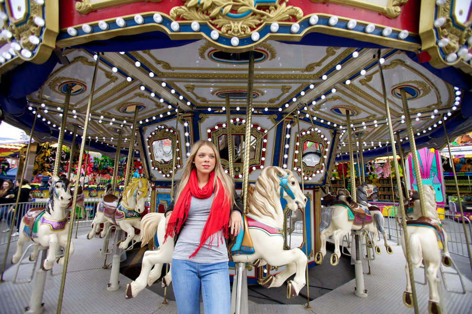 Fille devant un carrousel avec chevaux